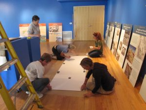 """Jane teaches """"Shaped by Water"""" exhibit crew how to install interpretive panels, 9/30/11."""