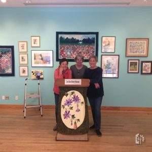 "Jane Reed, Diane Simmons and Julie Rose set up ""April in Bloom"" exhibit, April 6, 2019."