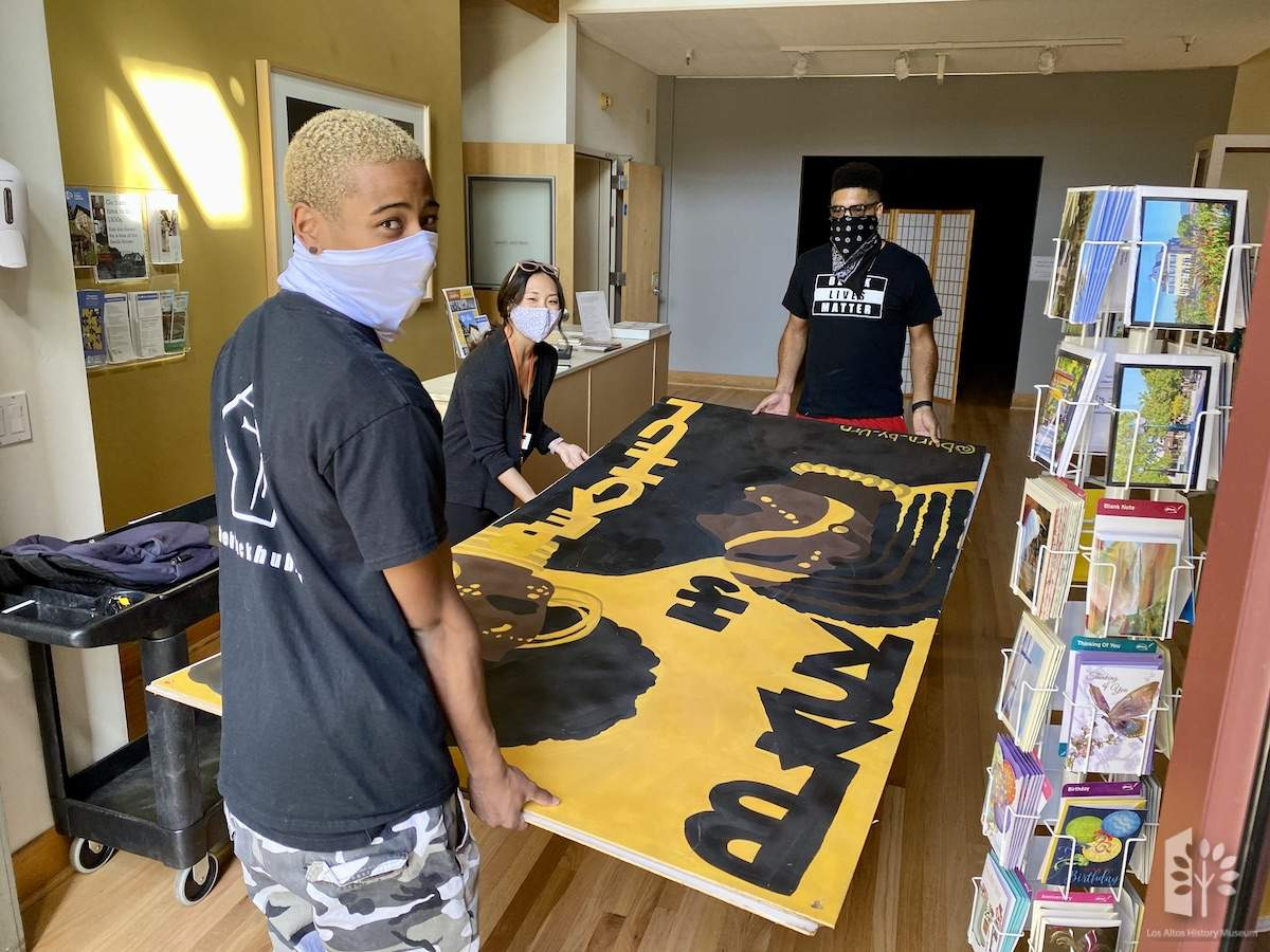 Kiyoshi Taylor, Dianne Shen and Kenan Moos assist with moving artwork into the Museum vault for the Social Justice Collection.